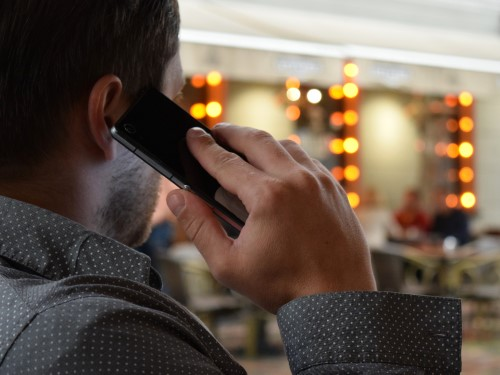 Advanced Call Queuing Personalized man in polka dot shirt holding cell phone to ear