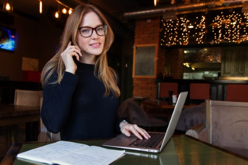 eight effective IVR characteristics woman working in cafe with phone and laptop