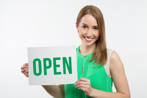 woman in green dress holding open sign to keep messages up to date