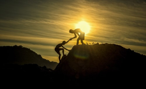 inclusive as possible teamwork at sunset mountaintop