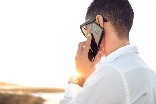 voice messages and customer communications man in white shirt holding black phone