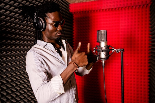 black man dreadlocks thumbs up recording booth microphone