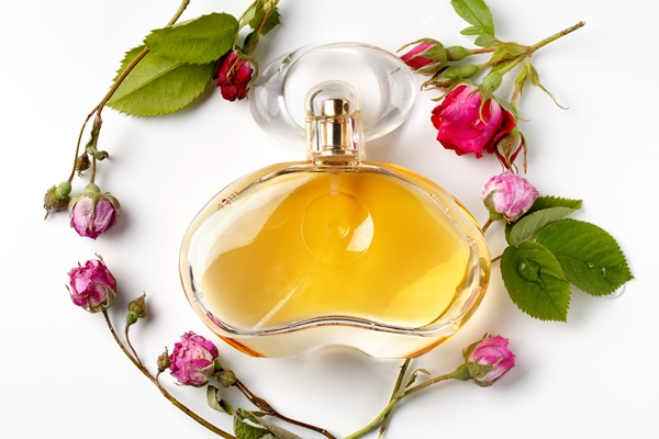 perfume bottle surrounded by roses
