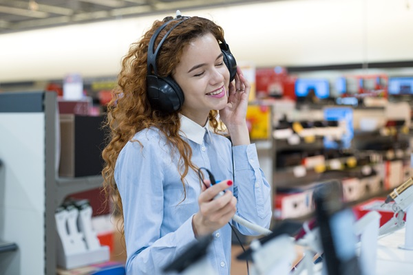 woman smiling headphone listening music store